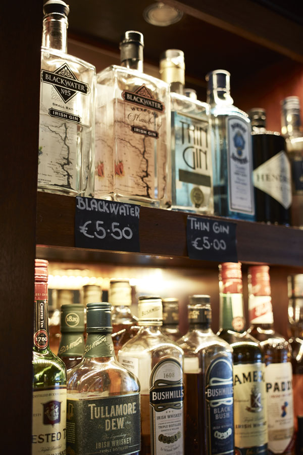 Bar shelving with alcohol bottles signage prices