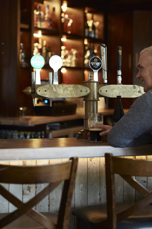 Bar details drinks seating, male customer enjoying pint of Guinness at bar counter