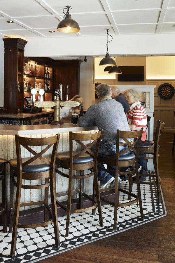Bar area,drinks, seating, tiling pendant lights, customers enjoying drink & chat at bar counter