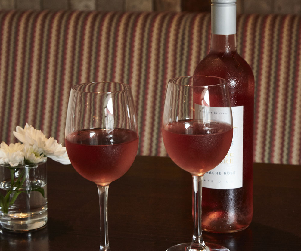 Bar, 2 wine glasses with rose wine and wine bottle on a table, comfortable seating with
