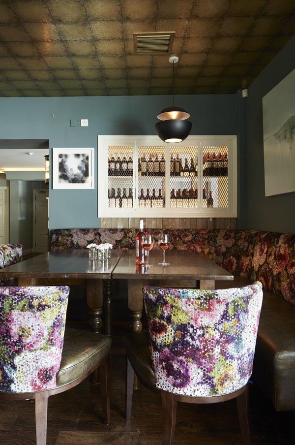 Bar seating area table comfortable seating timber panels pendant lighting, wall art