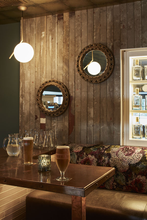 Bar counter, drinks, beautiful floral comfortable seating timber panels copper counter top, decorative wall mirrors