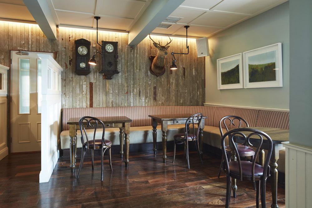 Bar seating tables timber wall paneling, pendant lighting, wall art, deer head wall display