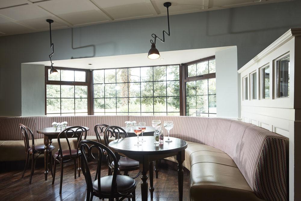 Bar comfortable seating tables around bay window, timber panels pendant lighting, timber flooring