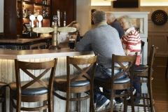 Bar area,drinks, seating, tiling pendant lights, customers enjoying drink & chat at bar counter