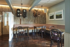 Bar seating tables timber wall paneling, pendant lighting, wall art, deer head wall display